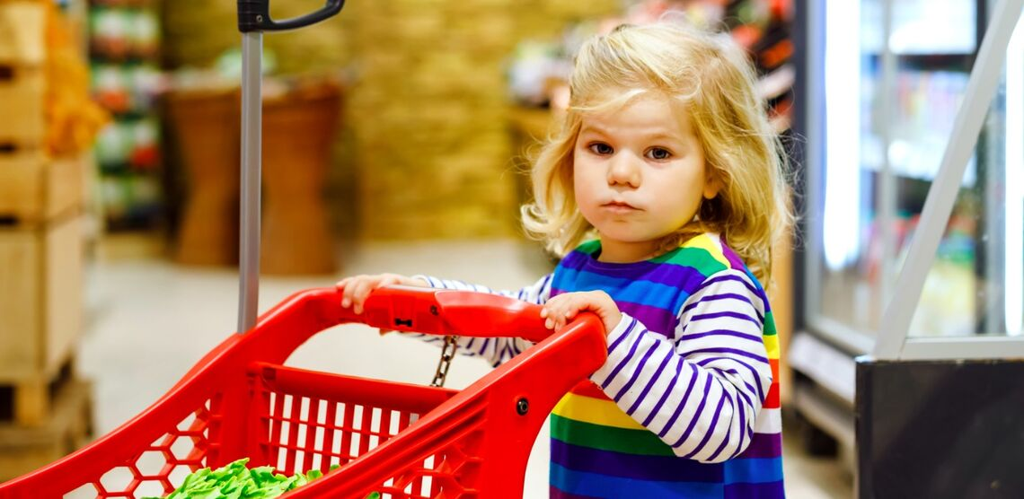 Little girl pushing cart in grocery store.