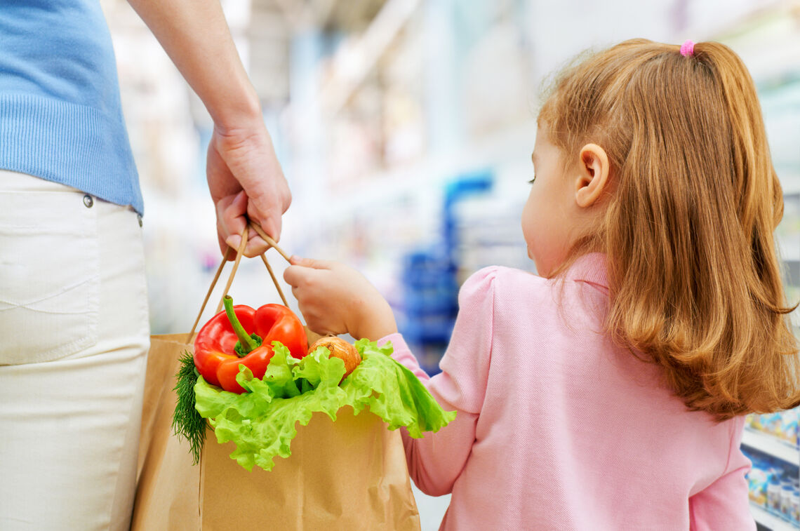 Parent and child holding a shopping bag with fruit & vegetables.